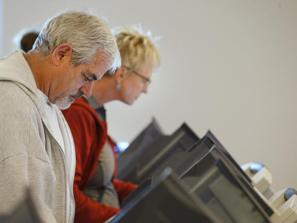 People cast their ballots on electronic voting machines at the Provo Recreation Center on Oct. 25, the first day of early voting in Provo, Utah.