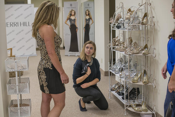 Kelly Borrelli shops for a dress for the Country Music Awards while Alia Bajorek shows her shoes at Joeval's Formalwear in Rochester. Joeval's owner Kathy Adams says that small businesses in New York suffer from the 8 percent sales tax.