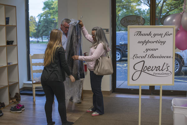 From left, Jordyn Adams hands Sheila Swartz the dresses she purchased at Joeval's Formalwear in Rochester. Adams helped her mother, Kathy Adams, to start this family business in 2011 and continues to work there while they expand to a second location.
