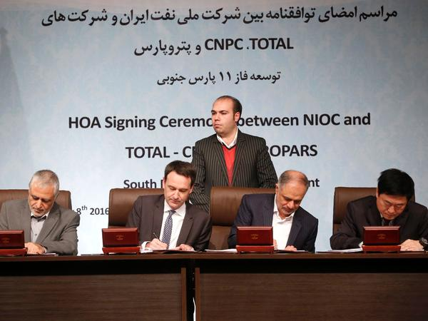 Iranian, French and Chinese officials sign a deal to develop a major offshore gas field in the Persian Gulf. It's the first big contract between Iran and a consortium led by a Western energy firm since sanctions were loosened in January.