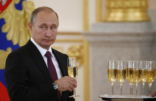 "Russian President Vladimir Putin holds a drink Wednesday at a Kremlin ceremony where he welcomed foreign ambassadors who recently arrived in Moscow. Putin said Moscow wants to restore good relations with the United States in the wake of the election of Donald Trump. But, he added, the current friction ""is not our fault."""