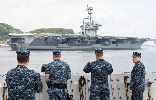 U.S. Navy servicemen see off the nuclear-powered aircraft carrier USS George Washington as it leaves the U.S. naval base in Yokosuka, Japan, in 2015.