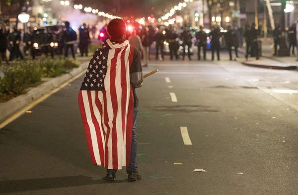 A protester wearing a U.S. flag faces police during a protest Wednesday in Oakland, Calif. Thousands of protesters rallied across the United States expressing shock and anger over Donald Trump's election, vowing to oppose divisive views they say helped the Republican candidate win the presidency.
