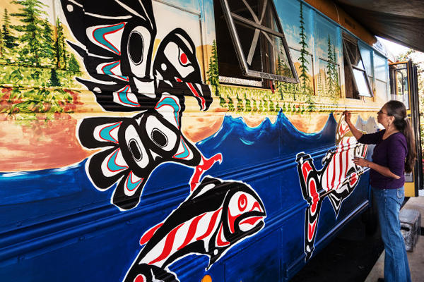 <p>Cat Whipple paints trees on the outside of a renovated school bus climate activists plan to deliver to Standing Rock protesters in North Dakota.</p>
