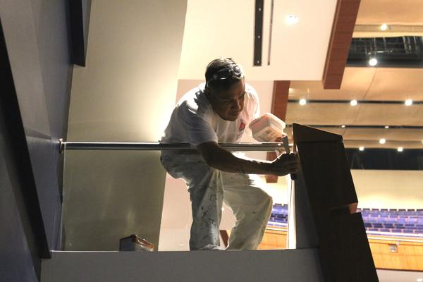 A worker makes some touch ups to a new box seat inside Robinson Center.