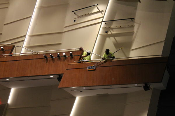 A worker cleans construction dust from the side of box seats inside Robinson Center.