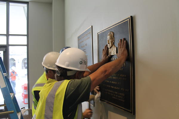 Workers mount the original dedication plaque for Robinson Center, which was named in honor of former Arkansas Governor and U.S. Senater Joseph T. Robinson