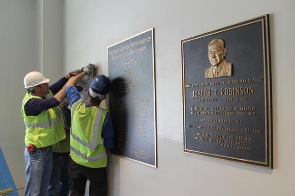 The dedication plaques for Robinson Center, including the original, one for this new renovation, and workers hang one from a 1970s renovation.