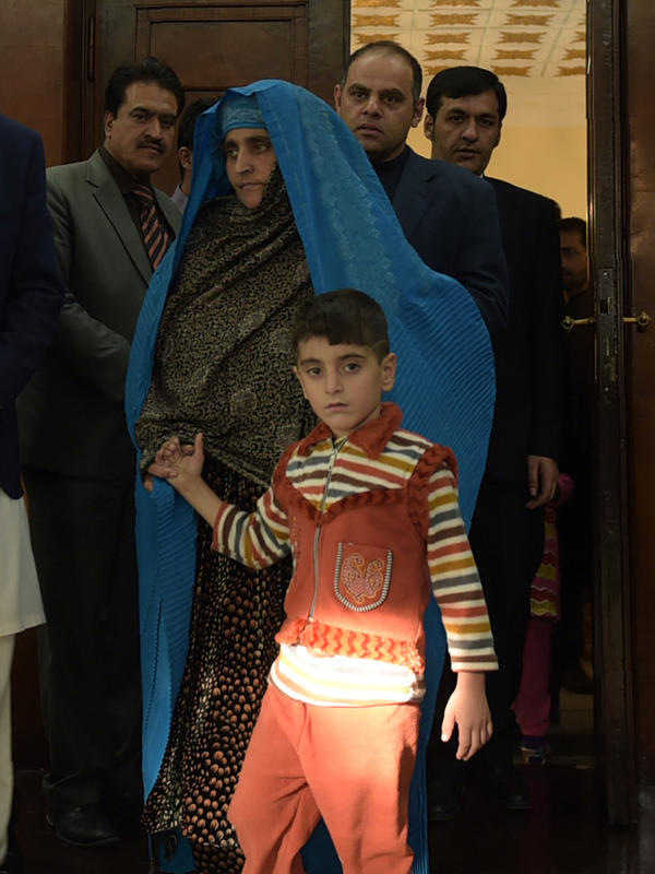 Afghan refugee Sharbat Gula (center) will get free medical care in India. She seen here arriving with her son at the Presidential Palace in Kabul before meeting with Afghan President Ashraf Ghani Wednesday.
