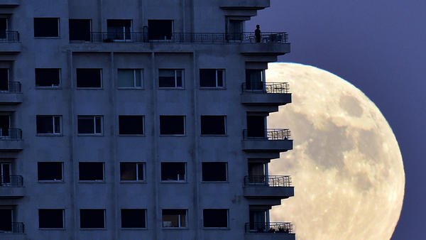 With the Nov. 13 supermoon rising in the background, a man looks out from a balcony in Madrid. At its closest pass to Earth, the full moon can look up to 14 percent bigger and 30 percent brighter, NASA says.