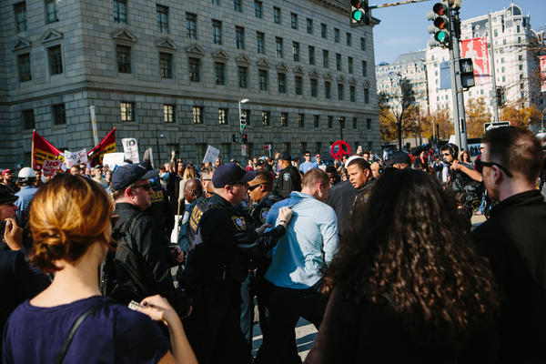 Protesters along 14th Street outside of the Reagan Building shout as police escort a man from the crowd after a brief confrontation.