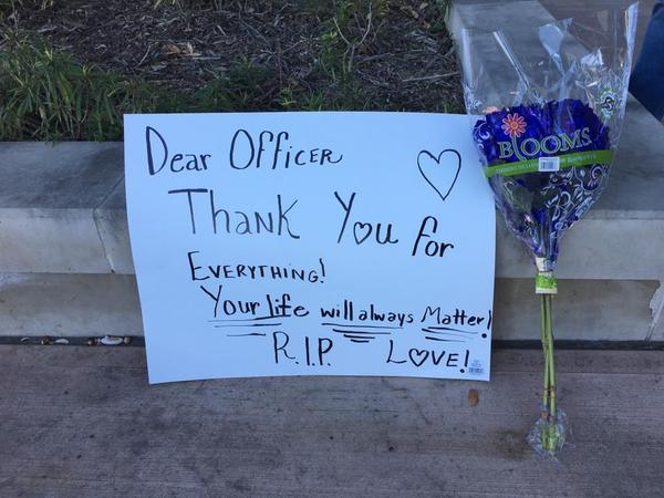Sign left at site of police officer shooting.