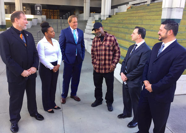 Attorneys representing Tony Gaiter (3rd from left) and 141 other retired NFL players answer questions in front of the U.S. Federal Courthouse in Fort Lauderdale on Nov. 21, 2016.