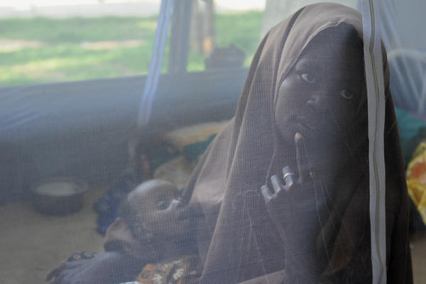 A mother and her 7-month-old daughter sit beneath a mosquito net at a hospital in Mogadishu, Somalia.