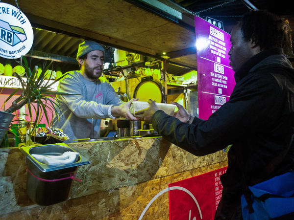 Junior Herbert, a volunteer with Olio, collects leftovers from vendors at London's Camden Market. London has become a hub for apps and small-scale businesses that let restaurants and food vendors share leftovers with the public for free, and otherwise reduce the amount of edibles they toss.