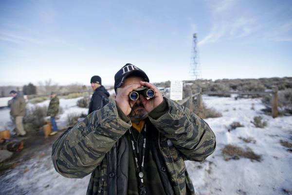 <p>Sean Anderson, of Idaho, a supporter of the group occupying the Malheur National Wildlife Refuge, looks through binoculars at the front gate Wednesday, Jan. 6, 2016, near Burns, Oregon.</p>