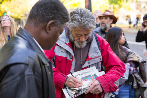 <p>Neil Wampler, right, signs a napkin outside the federal courthouse in downtown Portland.</p>