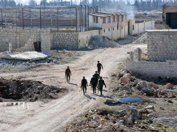 Syrian pro-government forces walk past damaged houses in eastern Aleppo, near Masaken Hanano, on November 23.