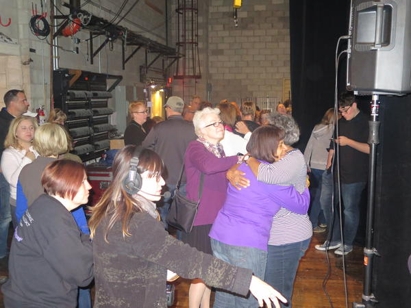 Members of the Harmony Project greet each other with hugs backstage.