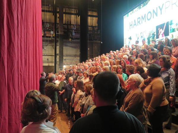 The 223 members of the choir get final instructions from David Brown before the curtain rises at tech rehearsal.