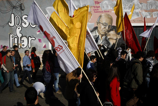 Workers wave flags and march in front of a Jose Saramago and Pilar del Rio graffiti tribute, in a recent protest against government austerity measures.