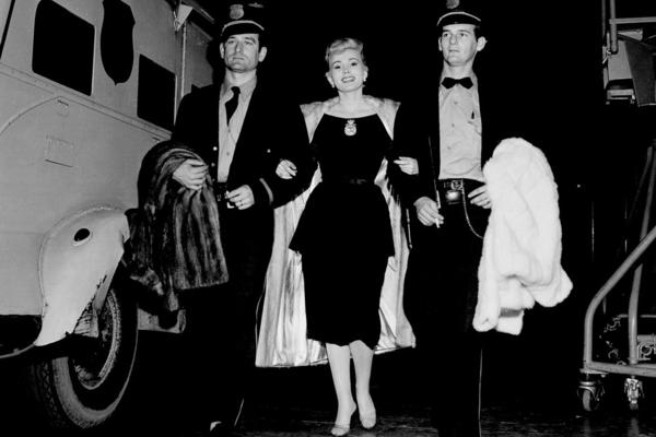 "Traveling with three fur coats and a $950,000 diamond known as the ""Shah of Persia,"" Gabor is escorted by two Brinks guards as she arrives at CBS's Television City in Hollywood on Dec. 1, 1955."