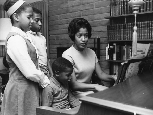 Myrlie Evers-Williams leads her three children — Reena (from left), Van and Darrell — at the family piano, circa 1965.