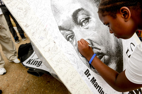 Shayna Mason, 11, signs a poster of King following a march down Pennsylvania Avenue.