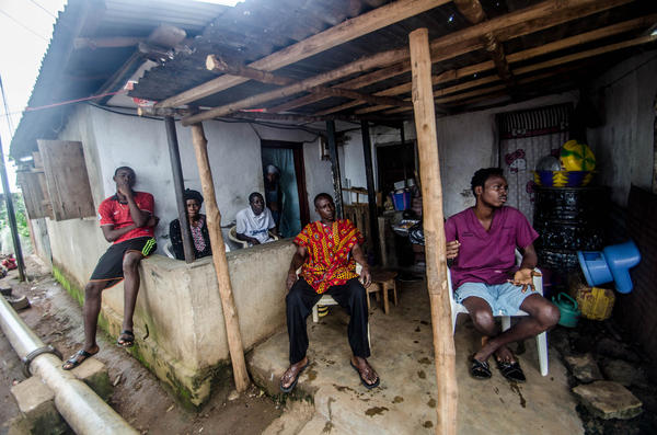 Members of the Koroma family relax Sunday at their quarantined home in Freetown.