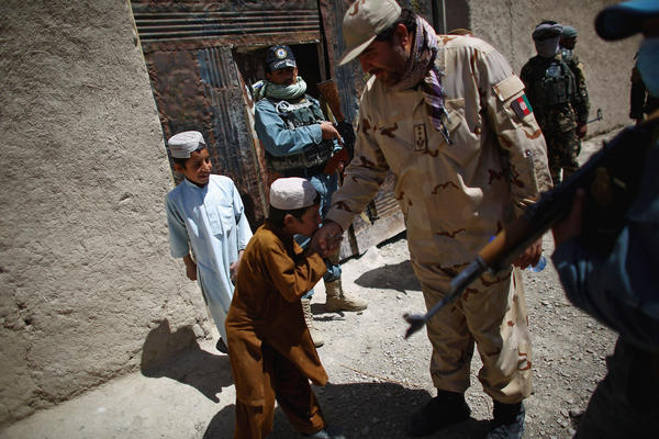 An officer with the local police greets a child in the village of Tazir Abad, a Taliban stronghold in Shah Joy district.