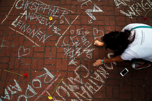 A woman pauses while writing the names of shooting victims in chalk in a park across from the iconic New York City gay and lesbian bar, The Stonewall Inn, on Monday in New York City.