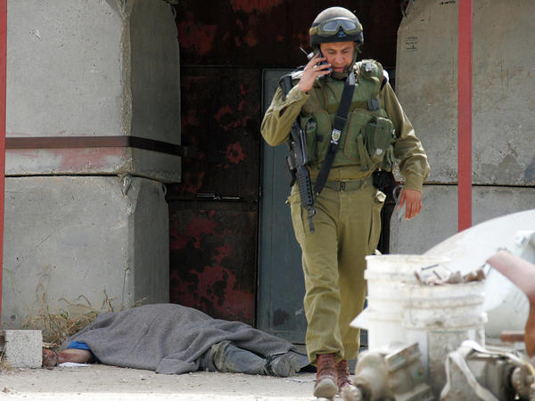 An Israeli soldier walks in front of the body of one of two guards who army sources said were killed by Palestinian militants on April 25, 2008. One of those killed was Eli Wasserman, 51.