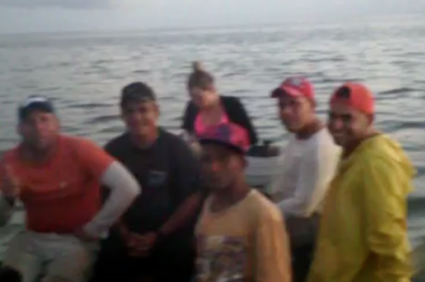 A screenshot of a video shows some of the 14 Cubans packed into a small wooden boat heading to Florida.