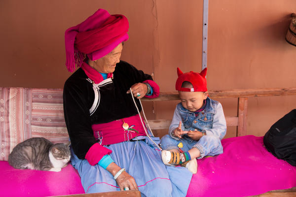 Zhaba Songding's grandmother, Ani Ciru, 77, sits with Zhaba's son Luosang Nyima, 2, and cat in their courtyard.