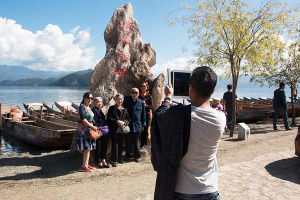 Tourists take photos by the water in Lugu Lake in southwest China. The area is home to the Mosuo ethnic group, which has one of the world's relatively rare matrilineal societies.