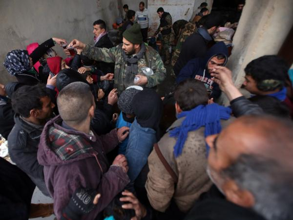 Syrians who fled from Aleppo's rebel-held areas queue to receive food on Dec. 1 at a shelter in the neighborhood of Jibreen, east of Aleppo.