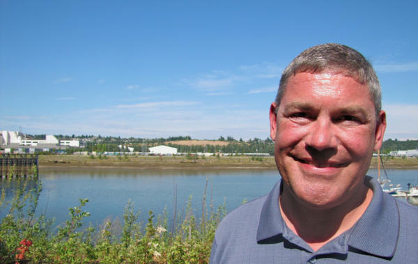 <p>Shawn Blocker stands across the Duwamish River from the former site of Boeing Plant 2, which was demolished in 2010.</p>