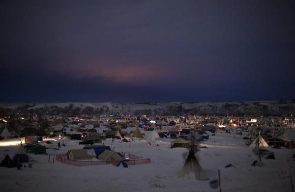 Though emergency evacuation orders have been issued by both the state of North Dakota and the Army Corps of Engineers, the three camps along the Cannonball River, now covered in snow, show no sign of packing up.