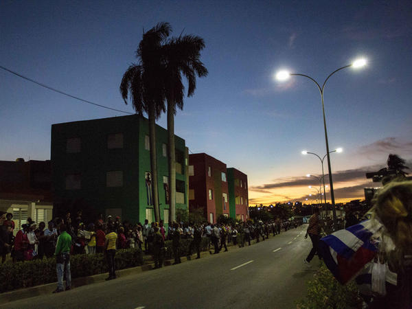 Crowds line the street leading to Santa Ifigenia cemetery as they wait at sunrise for the funeral procession carrying the ashes of Fidel Castro in Santiago, Cuba, Sunday.
