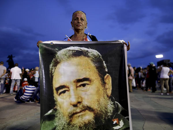A woman holds a picture of Fidel Castro before a rally honoring Cuba's late leader at Antonio Maceo plaza in Santiago, Cuba.