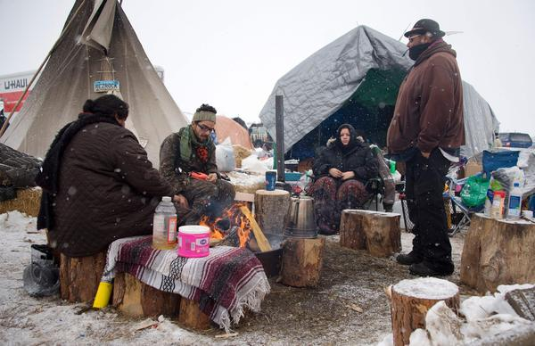 Protesters sit around a campfire as it snows at Oceti Sakowin camp on Monday.
