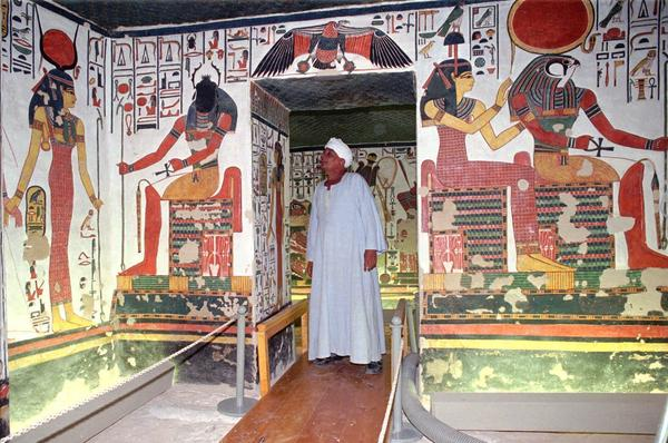 An Egyptian guard examines a doorway inside the tomb of Queen Nefertari in the Valley of Queens in Luxor, south of Cairo, in 1995.