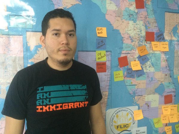 Julio Calderon, an organizer for the Florida Immigrant Coalition, beside a map of Florida with post-its for groups organizing for immigrants rights.
