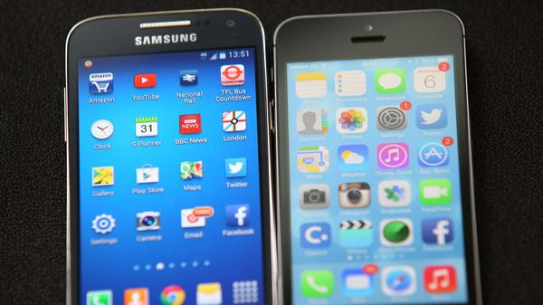 A Samsung and an Apple smartphone are displayed on Aug. 6, 2014, in London.