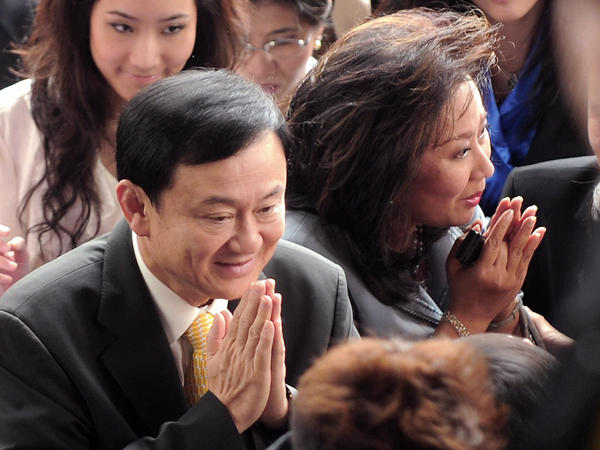 Thailand's deposed prime minister, Thaksin Shinawatra (left), and his wife, Pojaman, greet supporters on arrival at a court in Bangkok in July 2008. He was convicted on conflict of interest charges and lives in self-imposed exile.