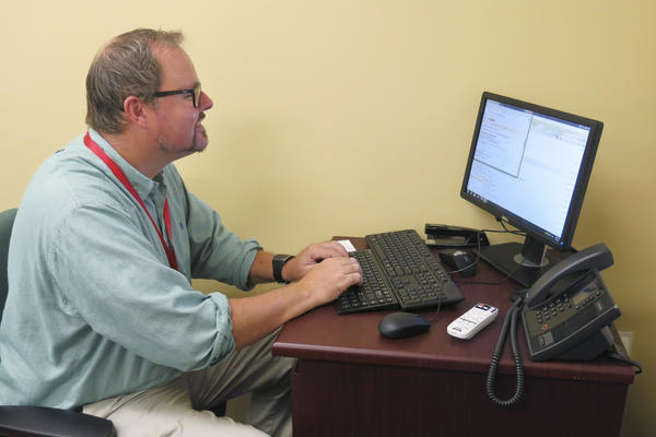English professor Neal Phillips sits at a Valencia campus computer in Orlando, Fla., crafting an email blast to students who've been flagged by a new program that analyzes how they're performing.