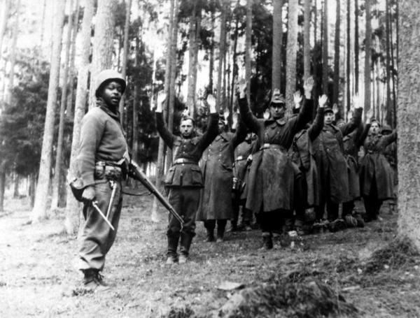 <p>A  U.S. soldier of the 12th Armored Division stands guard over a group of Nazi prisoners captured in the surrounding German forest. April 1945.</p>