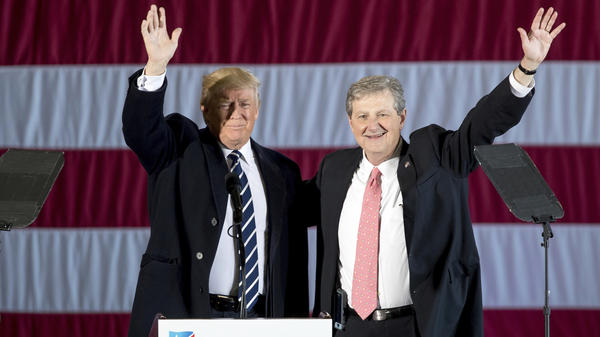 President-elect Donald Trump waves on stage with Louisiana Republican Senate candidate John Kennedy at a rally in Baton Rouge on Friday.