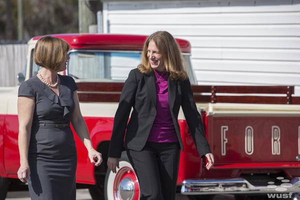 Health and Human Services Secretary Sylvia Burwell walks with U.S. Rep. Kathy Castor at Credit Xpress Auto Sales in Tampa.