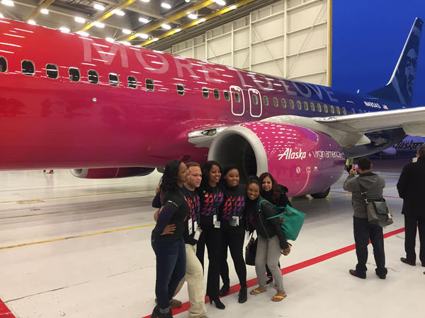 Alaska Airlines workers pose Wednesday in front of a Boeing 737 painted in a special livery to commemorate the merger with rival Virgin America.